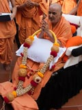 Swamishri with a garland offered by sadhus from the Sree Siddhaganga Mutt, Tumkur, Karnataka