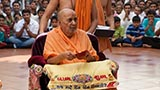 Swamishri holds a lamp in his hand