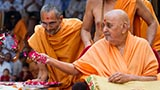Swamishri sanctifies shilas by showering flower petals and rice grains
