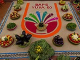 Vegetables arranged around a rangoli of the 'BAPS Yuva 60' logo