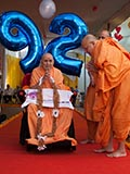Pujya Ishwarcharan Swami honors Swamishri with a garland