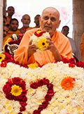 Swamishri holds a ball of flowers
