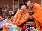 Swamishri plays drum sticks on the cake decorations
