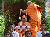 Pujya Mahant honor Swamishri with a garland