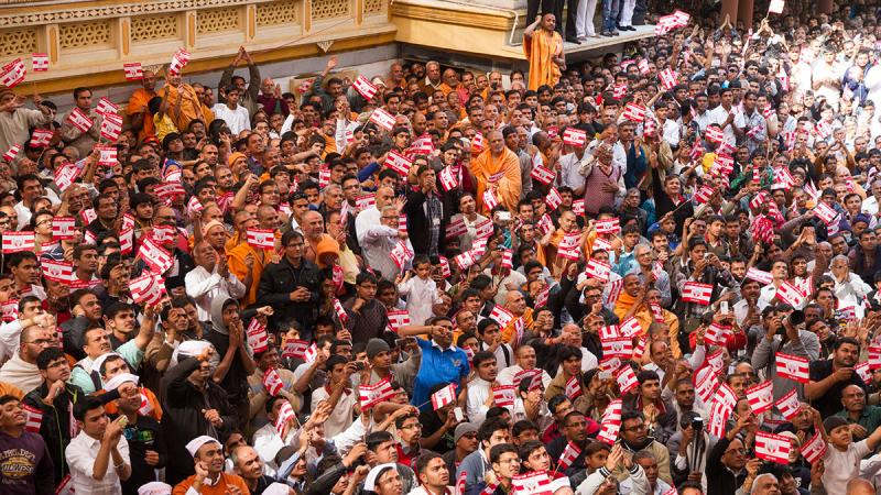 Sadhus and devotees wave flags commemorating 60 years of BAPS Youth Activities