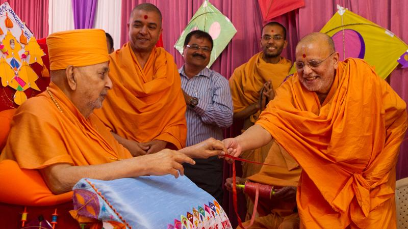 Pujya Ishwarcharan Swami gives the string of a kite in Swamishri's hands