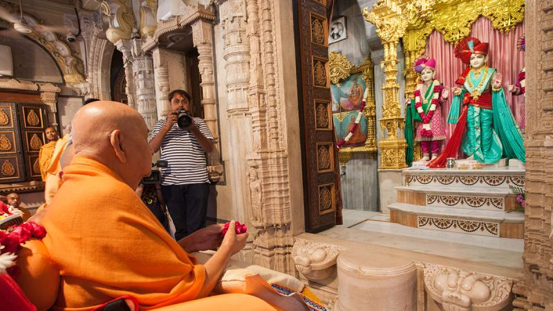 Swamishri offers a flower ball to Thakorji