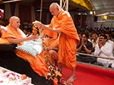 Pujya Mahant Swami honors Swamishri with a garland