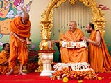Swamishri sprays colored water on Pujya Mahant Swami