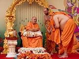 Swamishri sprays colored water on Pujya Ishwarcharan Swami