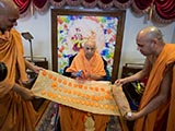 Swamishri is honored with a garland made of traditional sweets
