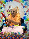 Swamishri playfully holds up a mock water jet