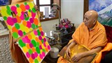 Swamishri sanctifies a card made by youths