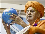 Swamishri holds the world globe
