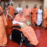 Swamishri in the mandir grounds during a rain shower