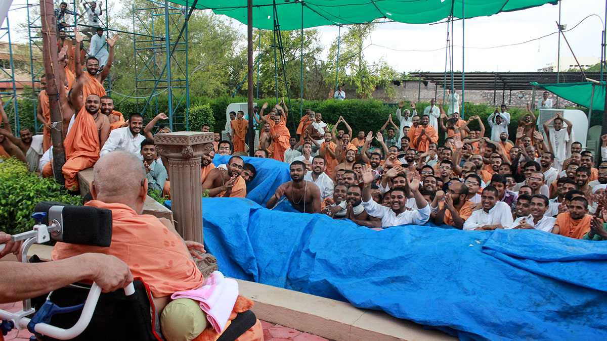 Sadhus and devotees doing darshan of Swamishri in the mandir grounds during the rain shower