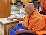 Swamishri reverentially touches holy charnarvind of Bhagwan Swaminarayan in Rangmandap