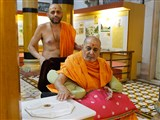 Swamishri reverentially touches holy charnarvind of Bhagwan Swaminarayan in Rang Mandap