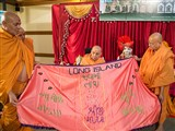 Sadhus honor Swamishri with a shawl on behalf of the devotees from Long Island, NY, USA