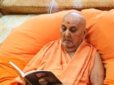 Swamishri reads the book released on Shri Harshadrai T Dave's centenary
