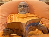 Swamishri reads the invitation card for inauguration of new shikharbaddh BAPS Shri Swaminarayan Mandir at Kolkata, India