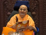 Swamishri reads the invitation card for inauguration of the new shikharbaddh BAPS Shri Swaminarayan Mandir at Mahuva, India - the birthplace of Brahmaswarup Bhagatji Maharaj