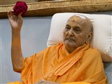 Swamishri sanctifies a ball of flowers