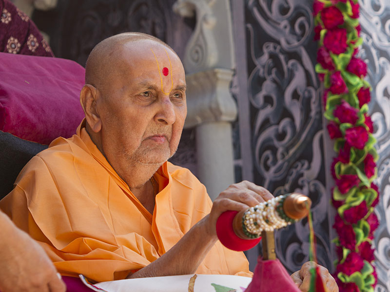 Swamishri starts spraying sanctified colored water on sadhus