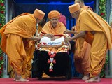 Pujya Kothari Swami and Pujya Tyagvallabh Swami honor Swamishri with a garland