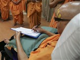 Swamishri reviews and signs a letter of guidance and blessings