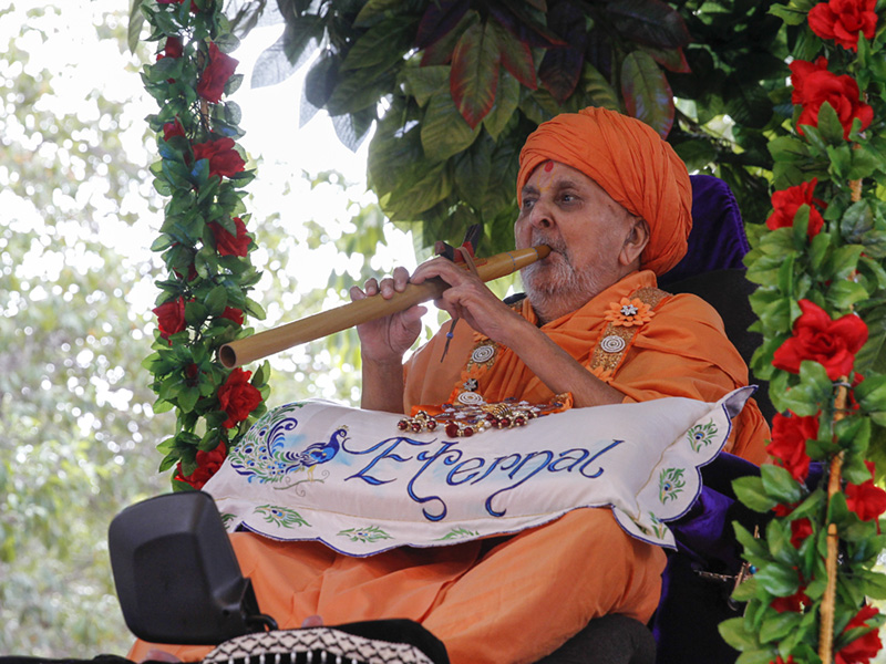 Swamishri plays a flute