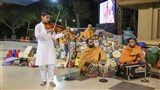 A child plays the violin before Swamishri