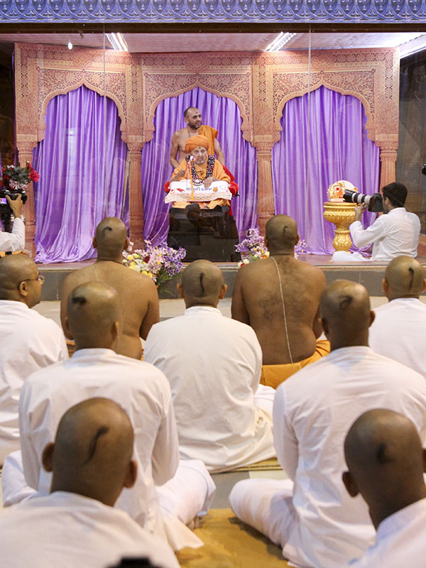 Swamishri arrives in the mandir grounds in the evening for the second diksha ceremony, to initiate three parshads as sadhus and seven sadhaks as parshads