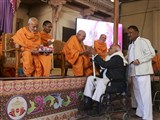Pujya Keshavjivan Swami (Pujya Mahant Swami) presents mementos to the devotees