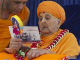 Swamishri reads an invitation card of Sarangpur Mandir Shatabdi Mahotsav