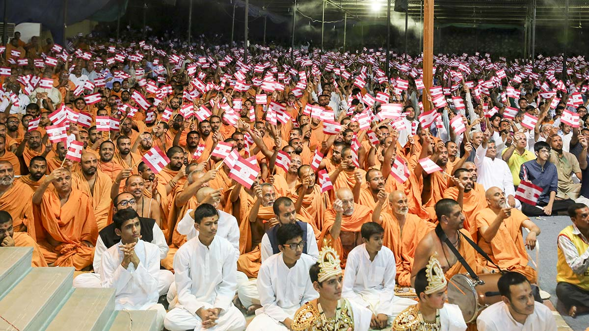 Sadhus and devotees wave BAPS flags