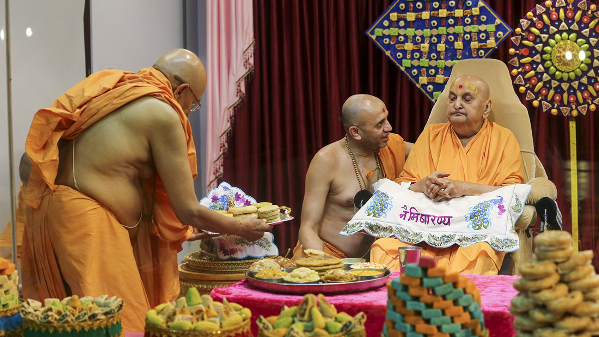 As a part of re-creating Annakut, Swamishri and Pujya Tyagvallabh Swami offer thal to Shri Harikrishna Maharaj
