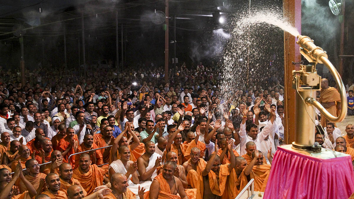 As a part of re-creating Pushpadolotsav, Swamishri sprays sanctified colored water on sadhus