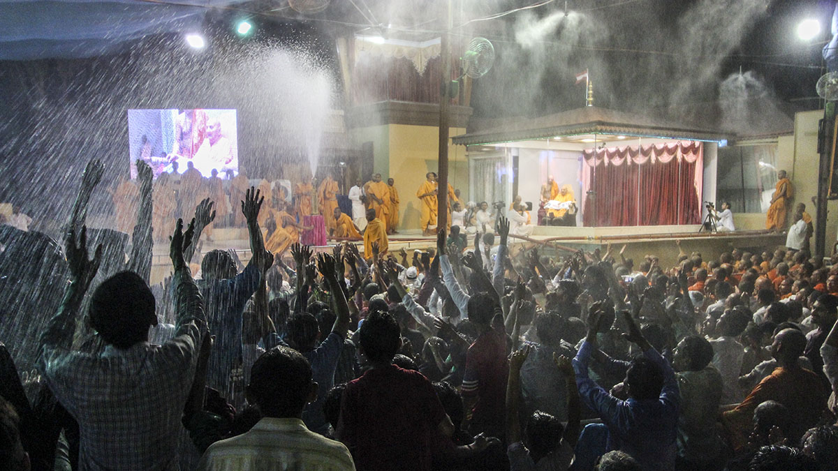 As a part of re-creating Pushpadolotsav, Swamishri sprays sanctified colored water on sadhus and devotees