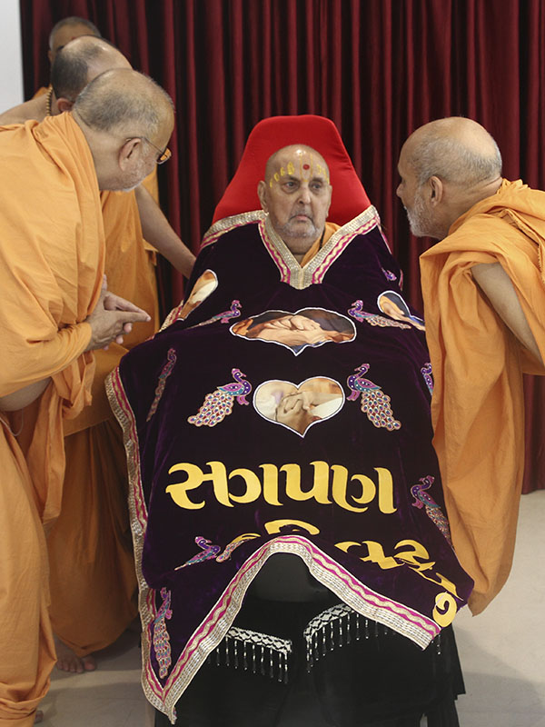 Swamishri is honored with a shawl by senior sadhus on Pramukh Varni Din