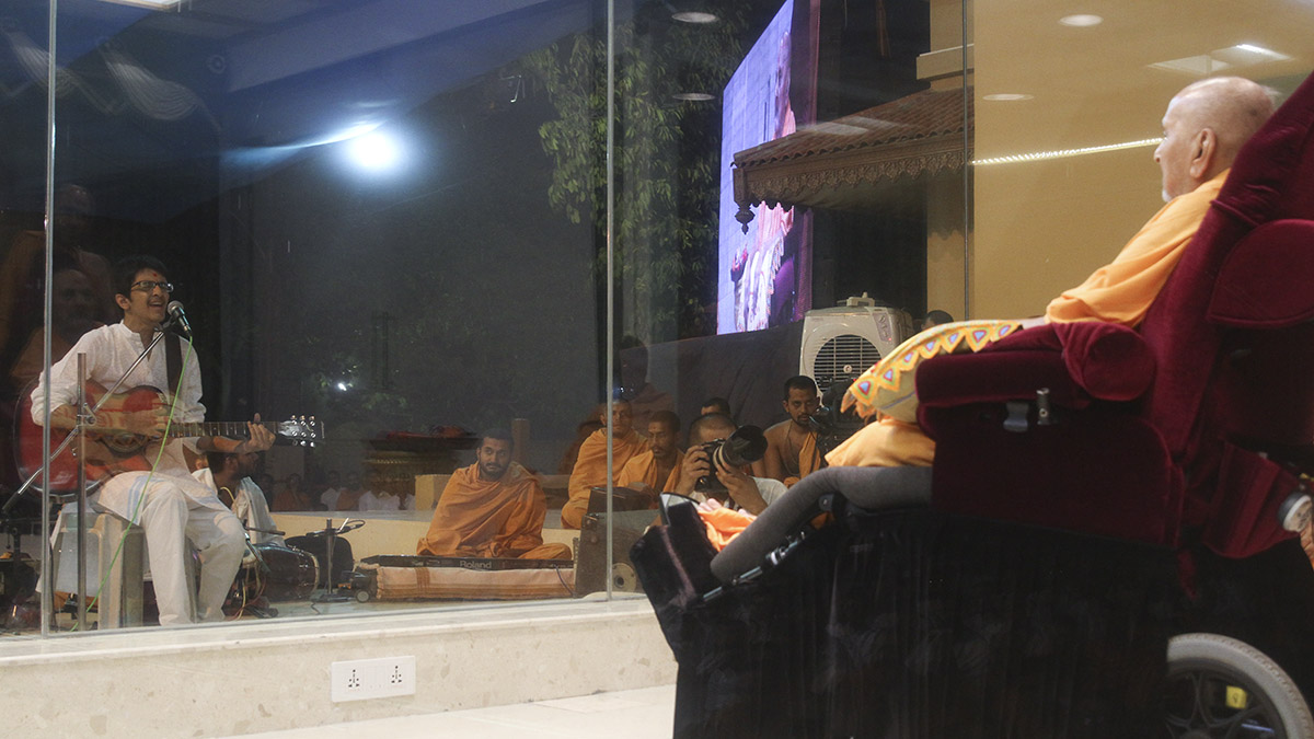 A youth sings a kirtan in front of Swamishri