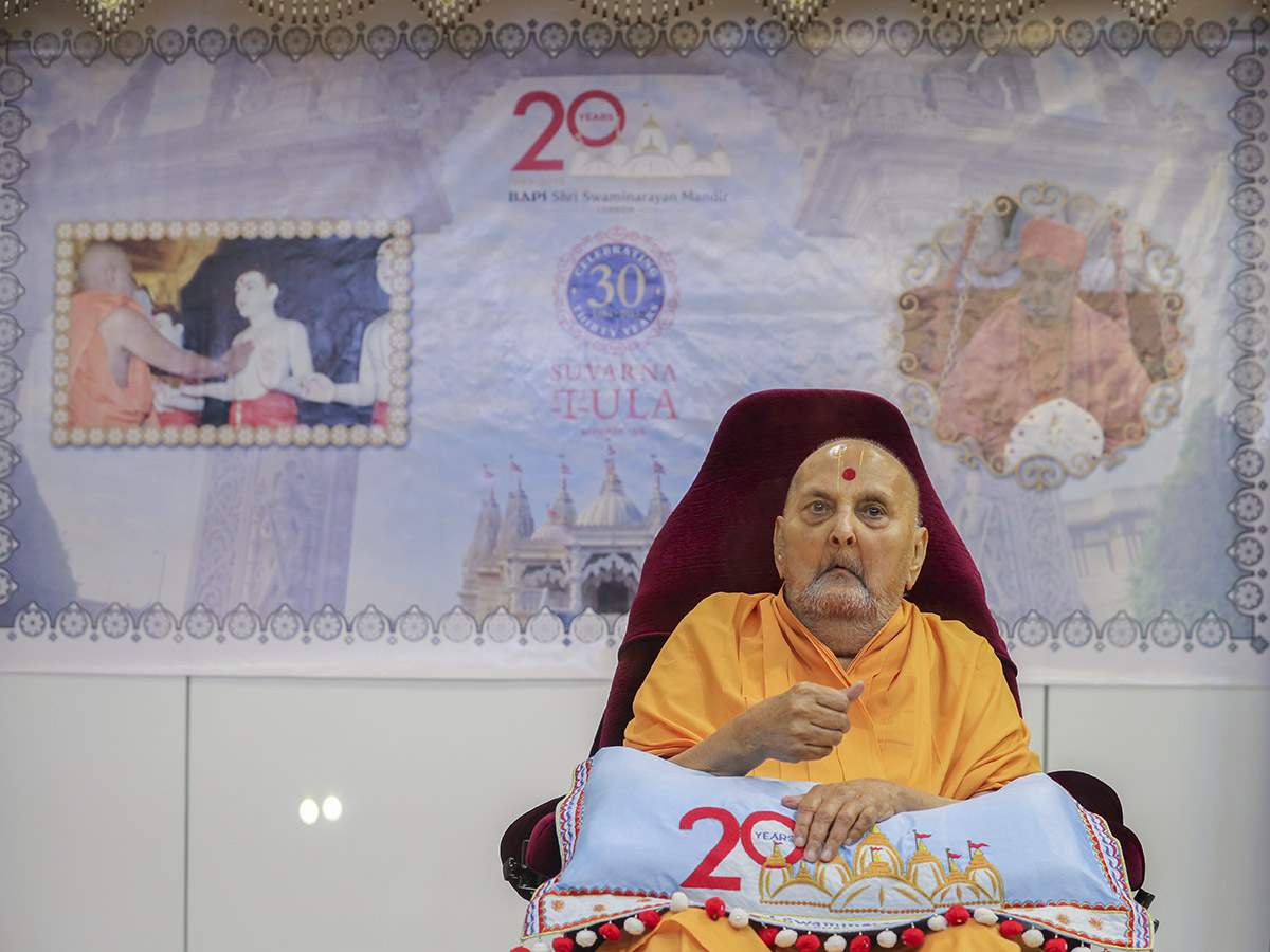 Swamishri arrives in the mandir grounds in the evening in front of a backdrop of the London Mandir 20 years and Suvarna Tula 30 years Celebrations