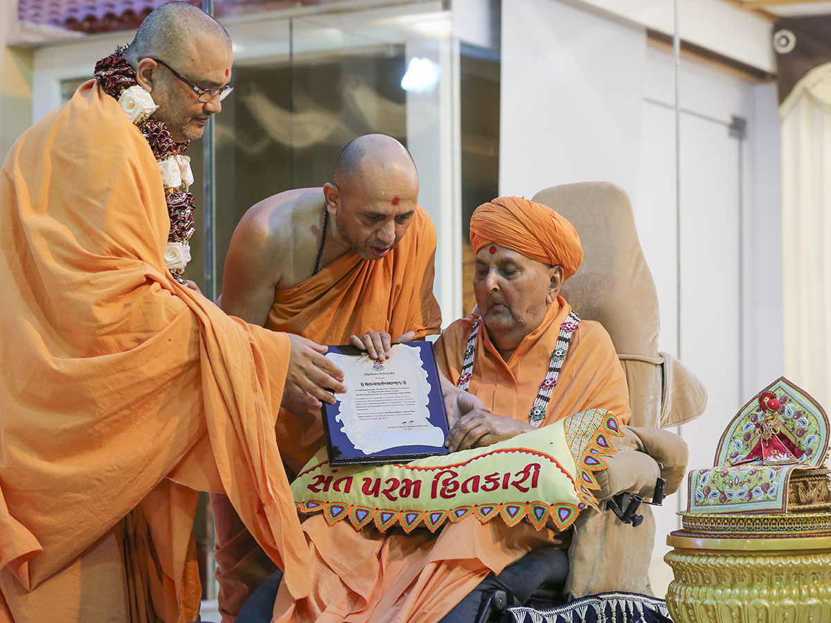 Swamishri sanctifies the 'Vedant Martand Sanman' awarded to Bhadresh Swami by Silpakorn University, Thailand