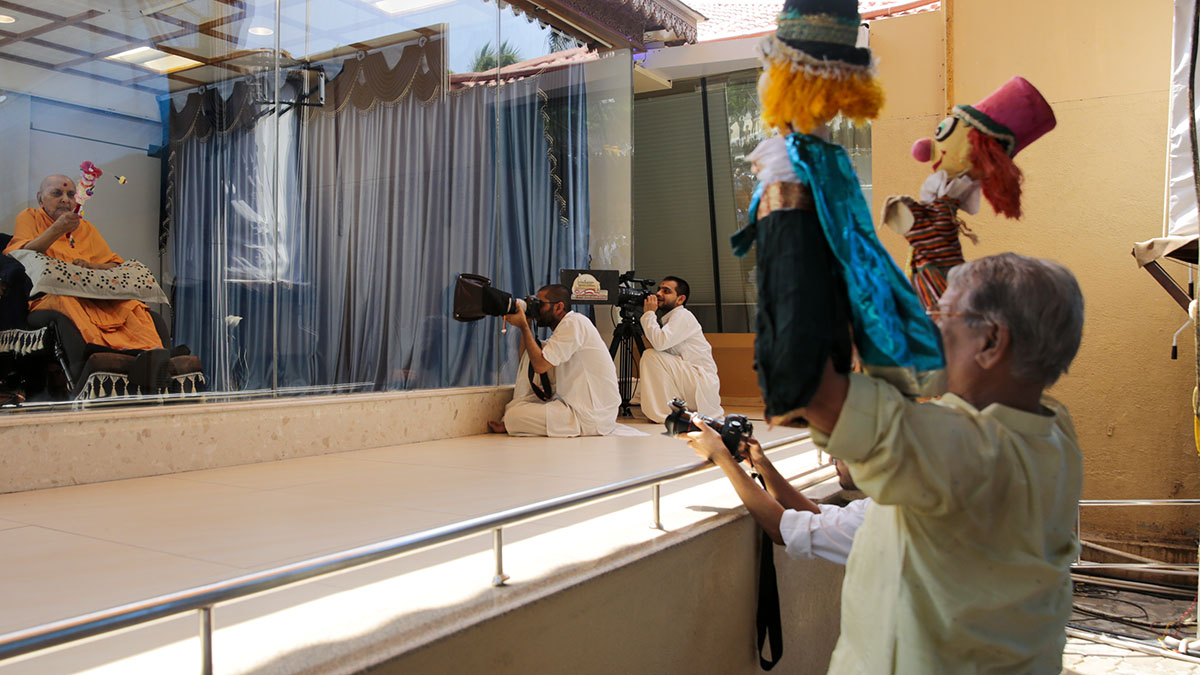 A devotee performs a puppet show before Swamishri