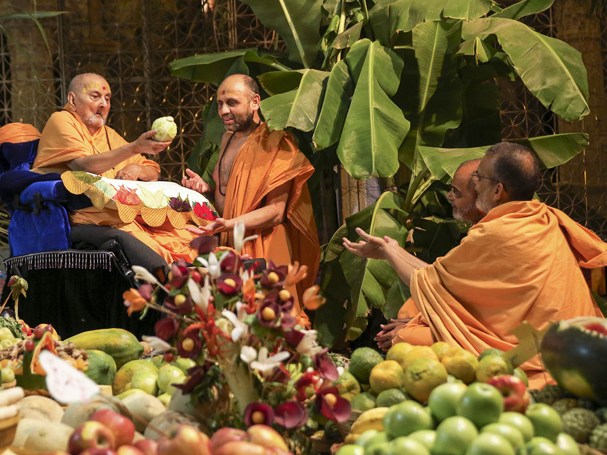 Swamishri holding various fruits and vegetables
