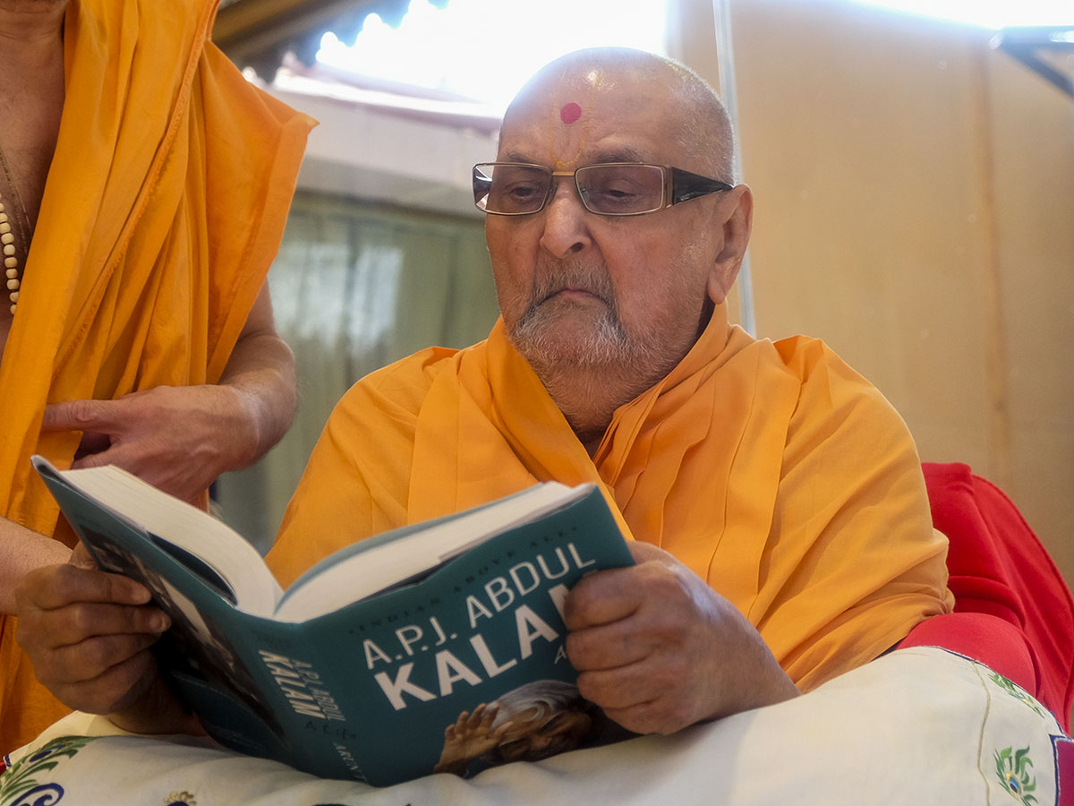 Swamishri reads book