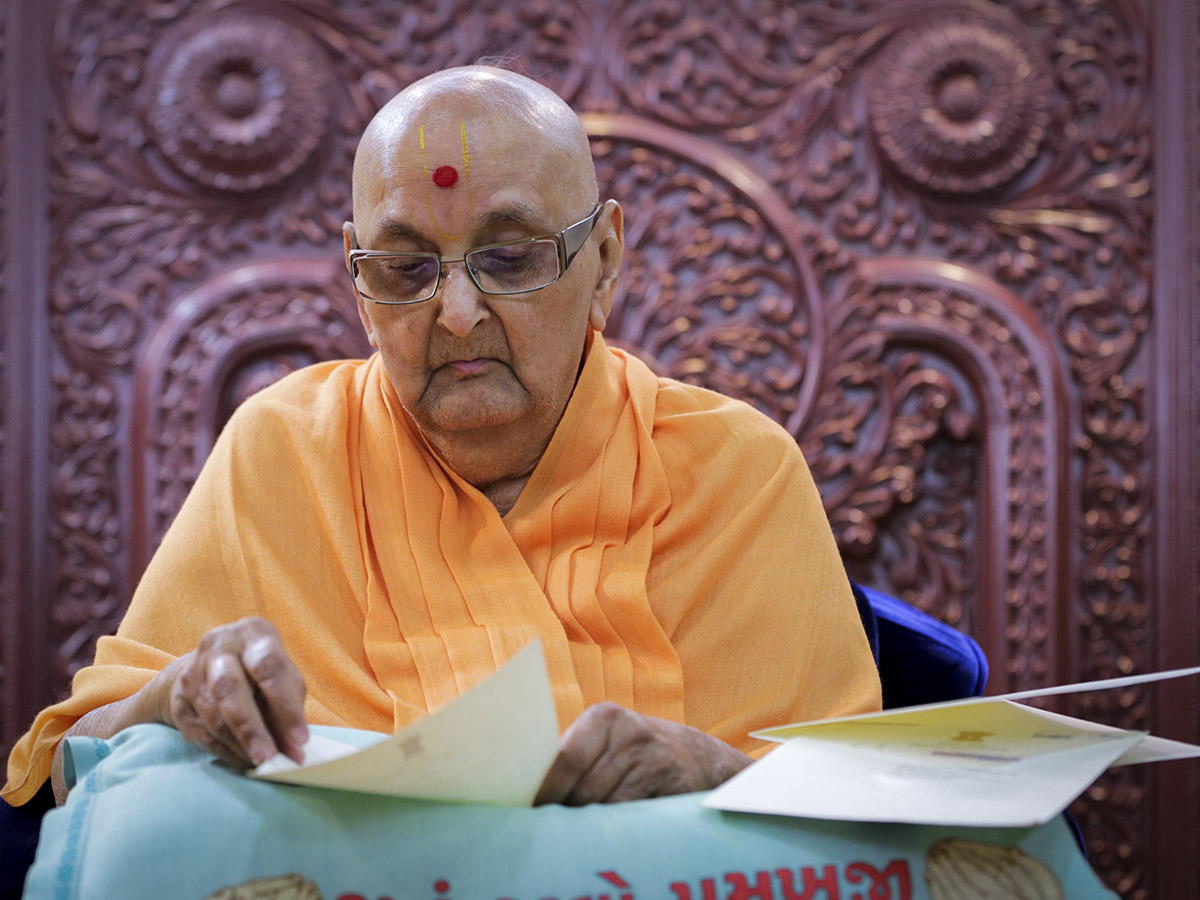 Swamishri in a divine mood while reading a letter