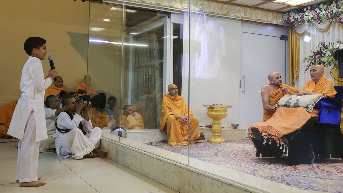 A child prays before Swamishri