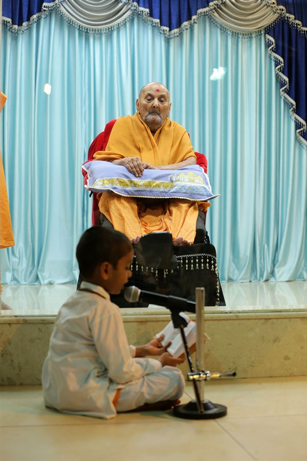 A five year old child reads the Vachanamrut before Swamishri