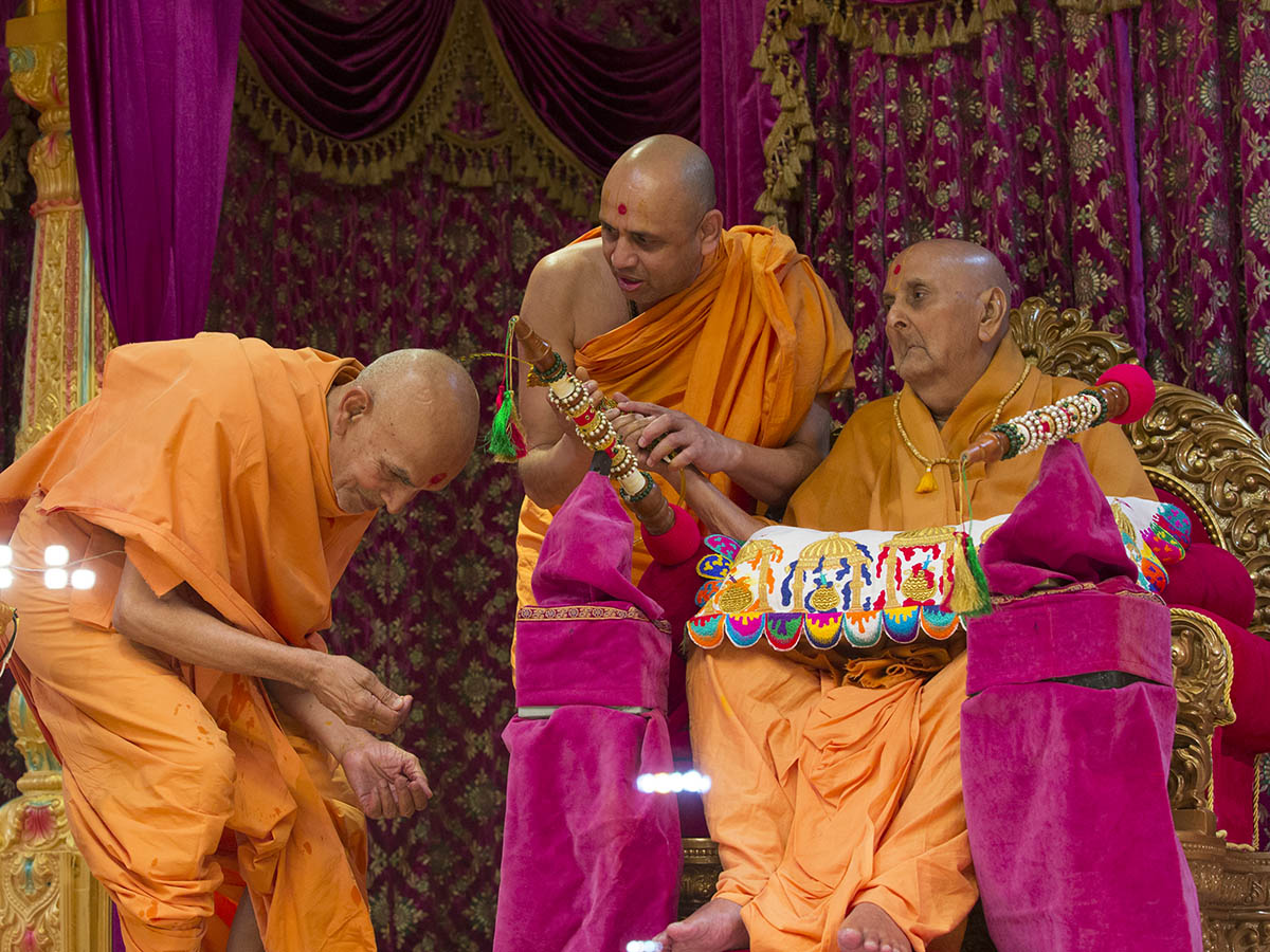 Swamishri showers sanctified colored water on Pujya Mahant Swami